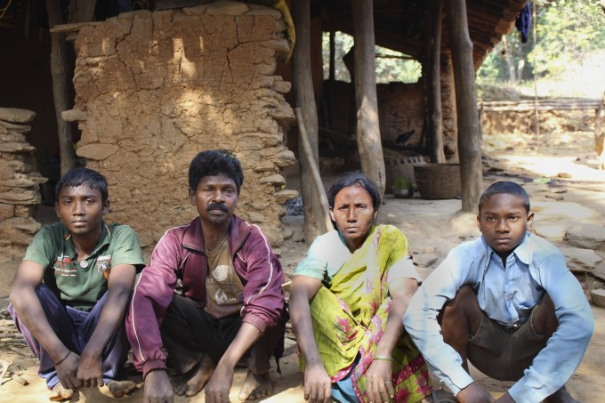 Ram Munda, his wife Kangla Munda, and their two sons sit in front of his mother's home, where two months ago his mother Suniya Munda was murdered along with his three siblings.