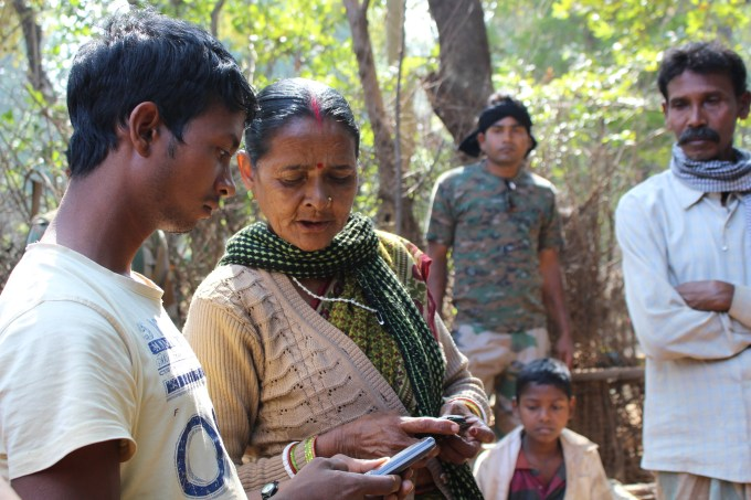 Chutni Mahto hands out her phone number to villagers gathered in Sasokara village, while police officers dressed in fatigues look on.
