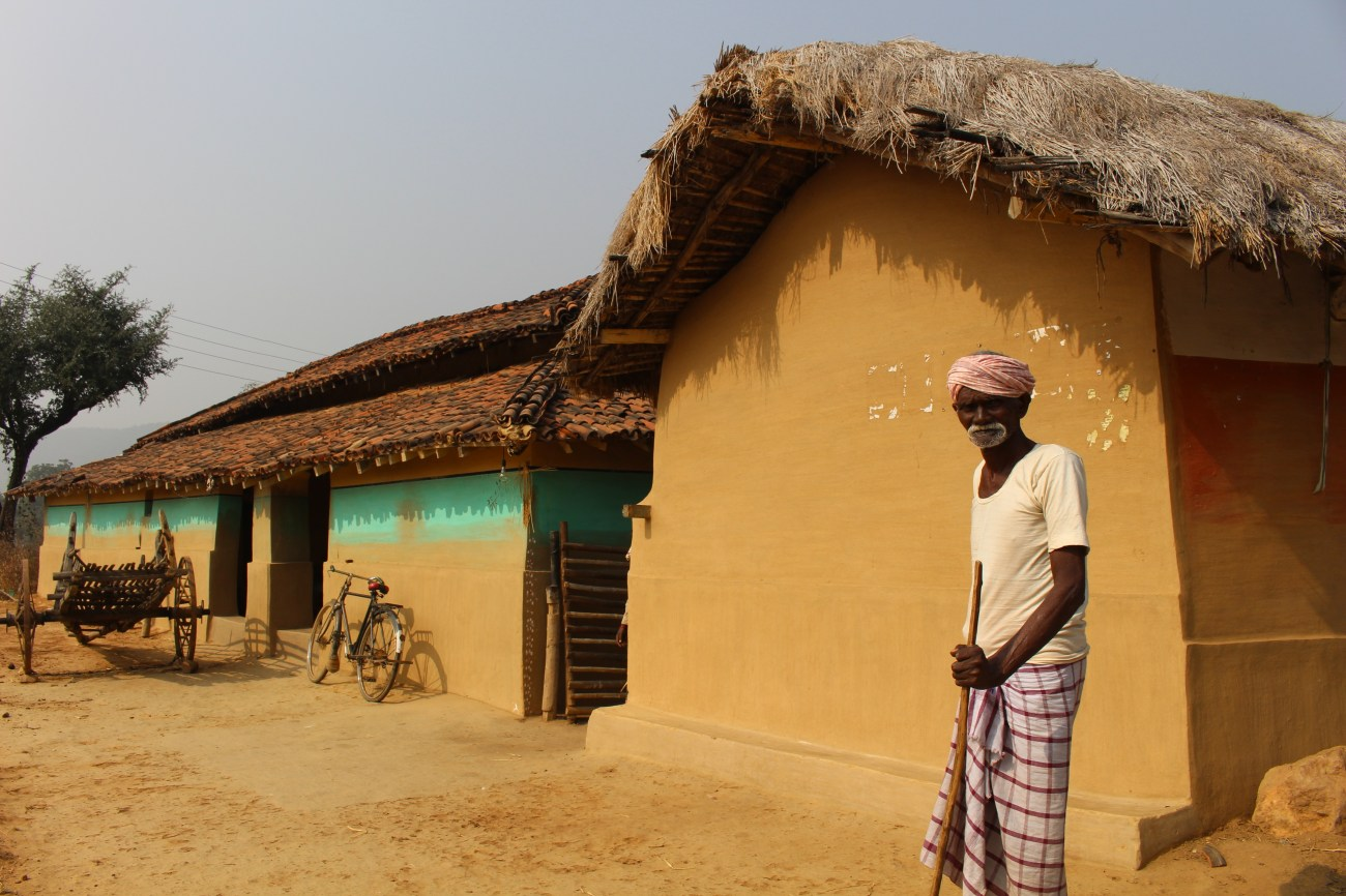 A farmer stands outside his home in Dumra, Jharkhand. Homes in the village are made of a mixture of mud, bricks, and concrete and painted in bright colors topped by roofs of red shingles and thatched hay.