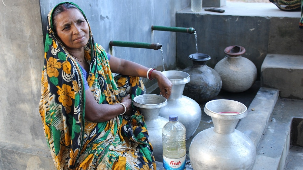 Savitri Mundo waits by the water pump in Fultala. Her husband, Bibhuti, now works in Dhaka as a security guard and comes home every three months [Neha Thirani Bagri/The GroundTruth Project]