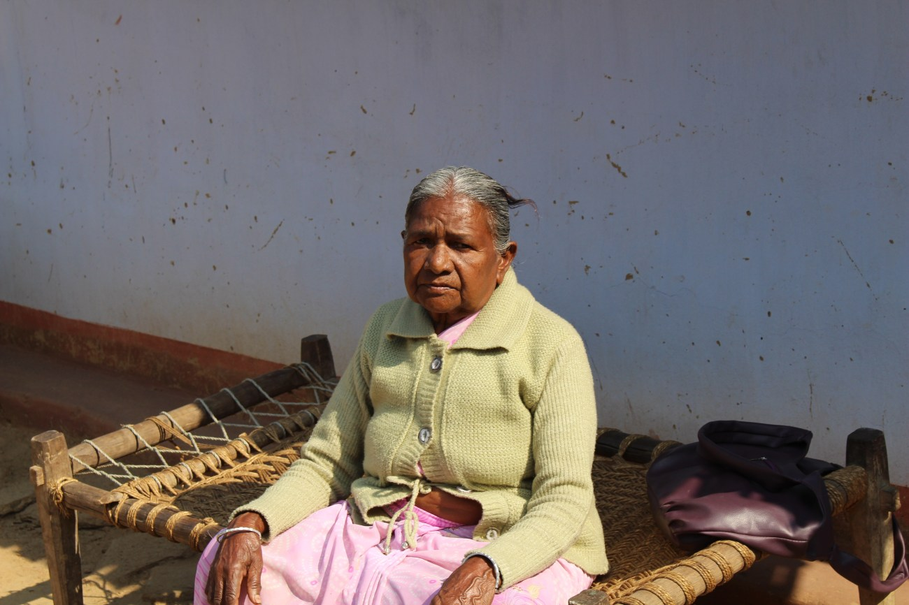 Surupadiya, who was accused of being a witch, sits in front of her home in the remote village of Bishtumpur. The allegation that she is witch has meant that the other villagers have shunned her, exacerbating her fear that the her neighbors, who called her a witch, will be able to attack her with impunity.