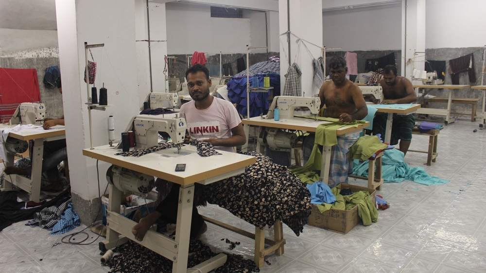 Khadija's husband Habibur sewing in a garment factory in Dhaka. He typically works 12 hours a day in the factory [Neha Thirani Bagri/The GroundTruth Project]