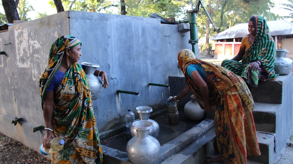 Women gather around the water pump in Fultala. In the rainy season, the line at the pump is shorter as women collect rainwater in plastic drums and pots.  [Neha Thirani Bagri/The GroundTruth Project]
