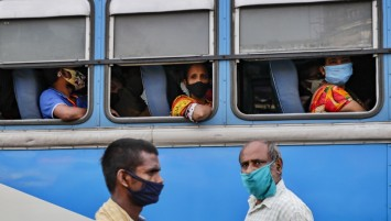 Commuters in a bus and pedestrians on the street wear masks in Kolkata, India. (Bikas Das / Associated Press)