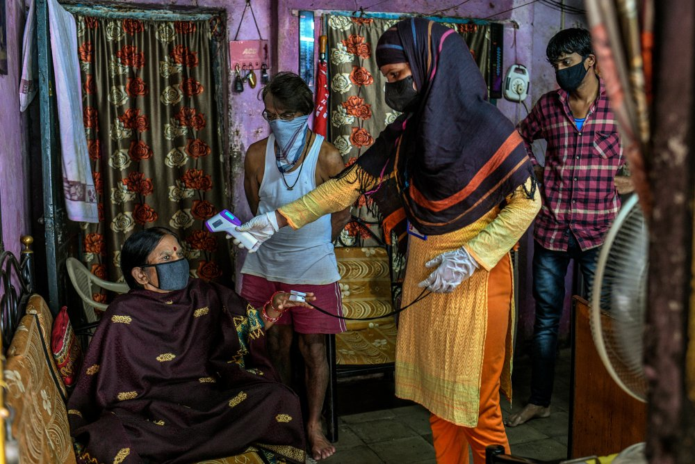 A health care worker checks a woman's temperature and oxygen saturation in the Dhole Patil slum on Aug. 10. (Atul Loke for TIME)