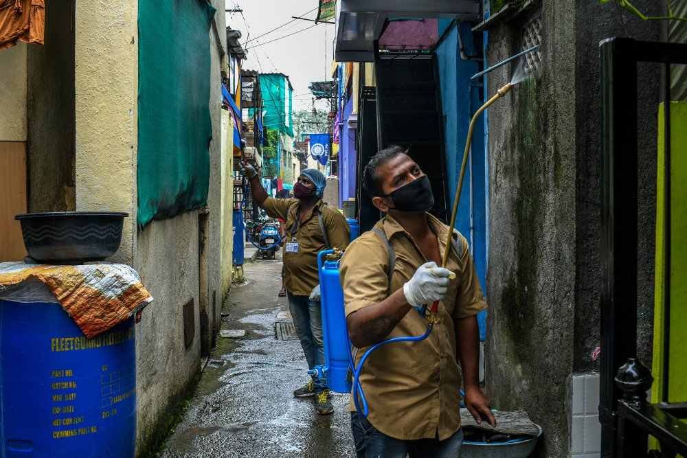 Workers from the Pune Municipal Corporation spray disinfectant in the Tadiwala Chawl area. (Atul Loke for TIME)
