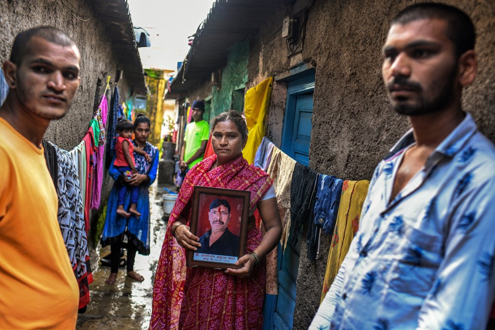 Kashinath Kale's widow, Sangeeta, flanked by her sons Akshay, left, and Avinash, holds a framed portrait of her late husband outside their home in Kalewadi, a suburb of Pune. Kale, 44, died from COVID-19 in July as the family desperately tried to find a hospital bed with a ventilator. (Atul Loke for TIME)