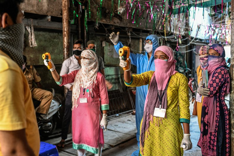 Health workers check residents' temperatures during a mass screening for COVID-19 symptoms in Dharavi in April. (Atul Loke—Panos Pictures/Redux)
