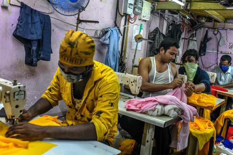 """""""My family was worried about the disease and didn't want me to return to the city, but I had to come back to work,"""" said Ishrar Ali, who stitches women's tops in a garment workshop in Dharavi. (Atul Loke for TIME)"""