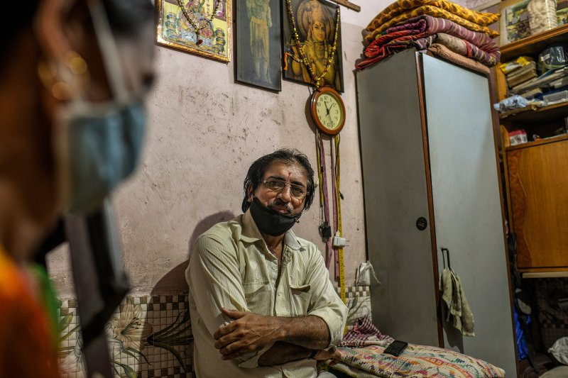 Jayanti Keshav Parmar, a tailor, at his home in Dharavi. His sewing machine sits idle, as no one in the neighborhood can afford to have new clothes stitched this year. (Atul Loke for TIME)