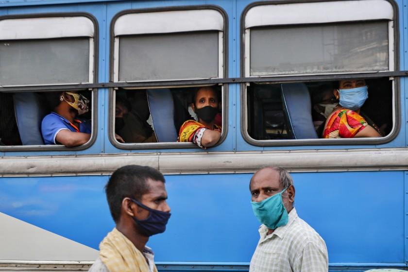 Commuters in a bus and pedestrians on the street wear masks in Kolkata, India. (Bikas Das / Associated Press)