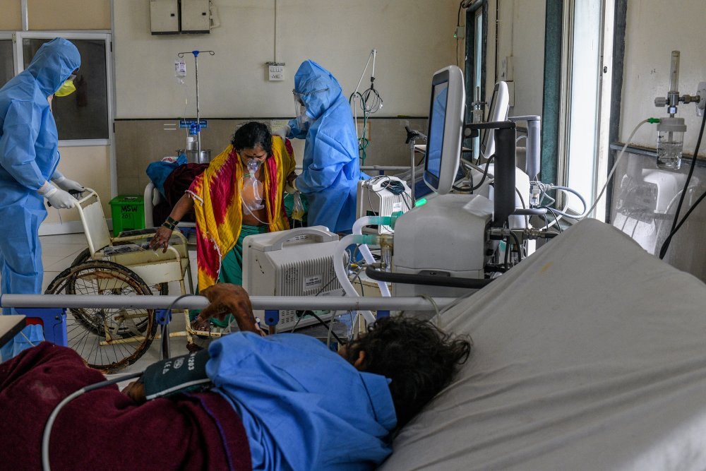 After her condition improved, a COVID-19 patient is helped into a wheelchair so she can be transferred from the intensive-care unit to an observation ward. (Atul Loke for TIME)
